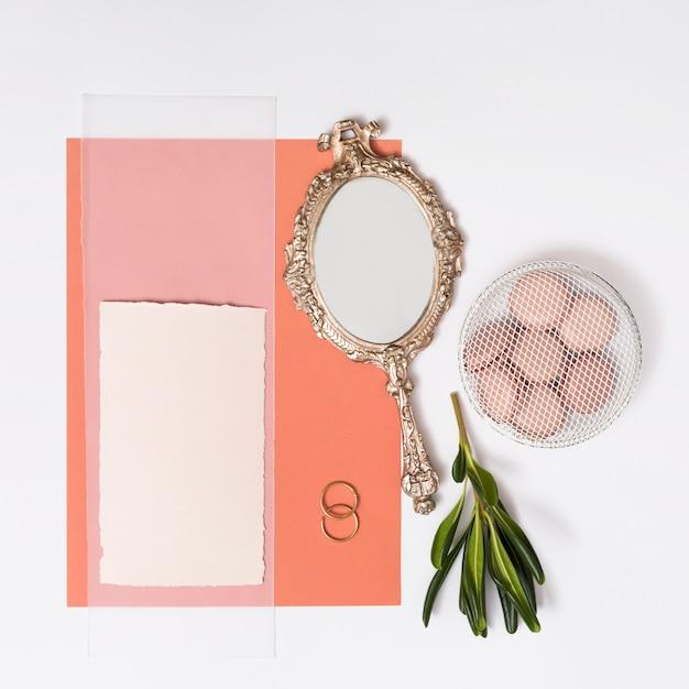 Ensemble de papiers près de macarons sur assiette, bagues et miroir Photo gratuit