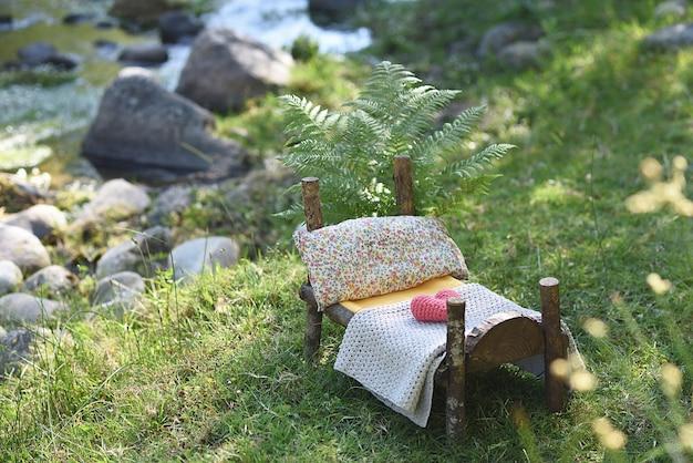 Ensemble De Photographie De Nouveau-né En Plein Air Avec Lit En Bois Dans La Nature Avec Des Fougères. Photo Premium