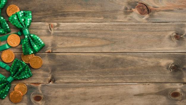 Ensemble de pièces d'or et de noeuds papillon sur planche de bois Photo gratuit