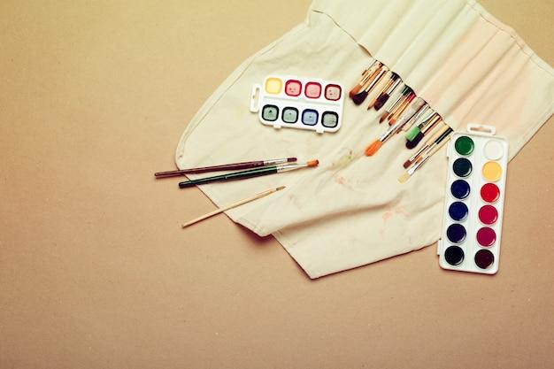 Ensemble de pinceaux d'artiste professionnel d'aquarelle dans un étui fait main et peintures d'aquarelle se bouchent Photo Premium