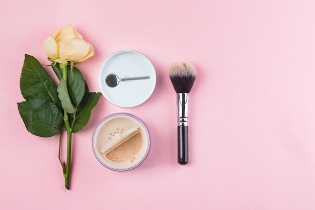 Ensemble de poudre de cosmétiques et pinceau avec rose sur fond rose. Photo Premium