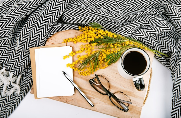 Ensemble de printemps avec des fleurs jaune plaid mimosa tasse avec des cartes postales de café stylo lunettes Photo gratuit