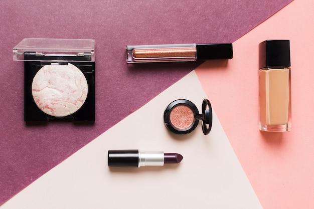 Ensemble de produits cosmétiques décoratifs sur une surface colorée Photo gratuit