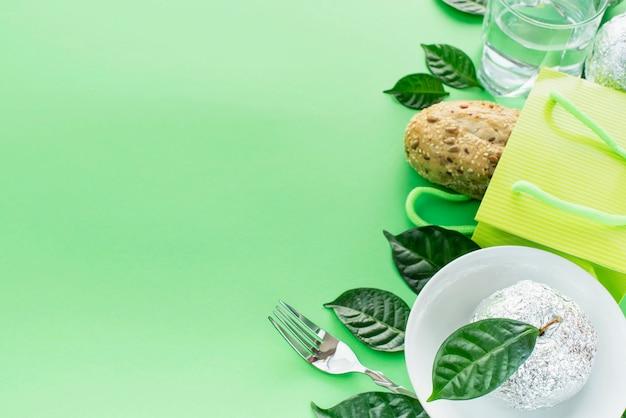 Un ensemble de produits sains écologiques pain frais eau verre verre pomme feuilles vaisselle. Photo Premium
