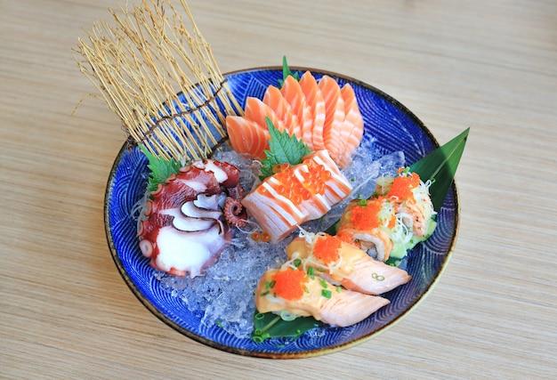 Ensemble de sashimi servi sur glace contre une table en bois. nourriture japonaise. Photo Premium