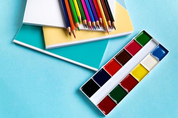 Ensemble scolaire de cahiers, crayons de couleur et aquarelles sur fond bleu avec espace de copie. vue de dessus Photo Premium