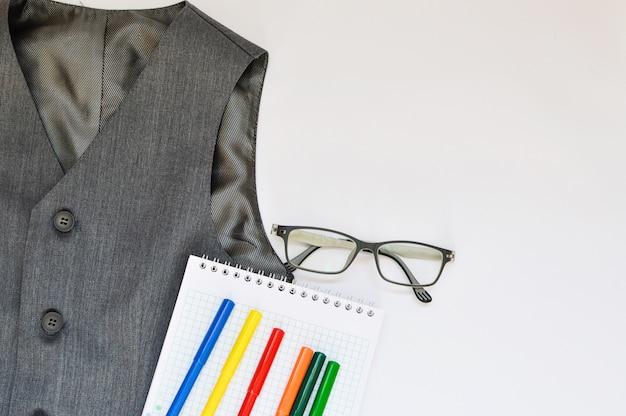 Ensemble scolaire avec gilet, crayons, feutres et lunettes sur fond blanc. Photo Premium