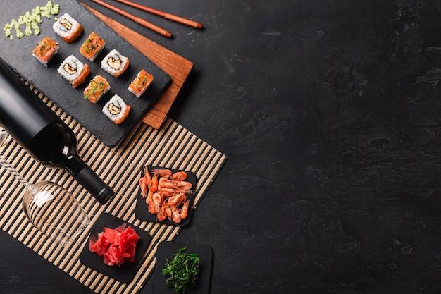 Ensemble de sushi et maki avec une bouteille de vin sur la table en pierre. vue de dessus Photo Premium