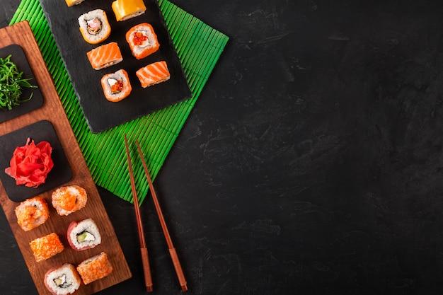 Ensemble de sushi avec wasabi et gingembre sur un plateau en pierre noire sur une table noire. vue de dessus Photo Premium