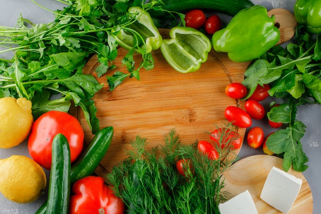 Ensemble De Tomates, Sel, Fromage, Poivron Vert, Citron Et Légumes Verts Sur Une Planche à Découper Sur Une Surface Grise Photo gratuit