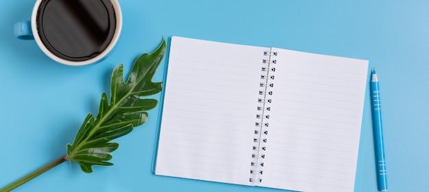 Ensemble de travail bleu de bloc-note, stylo, feuille verte et tasse à café, vue de dessus Photo Premium