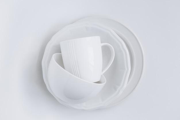 Ensemble d'ustensiles blancs dans une pile de trois assiettes différentes et une tasse Photo gratuit