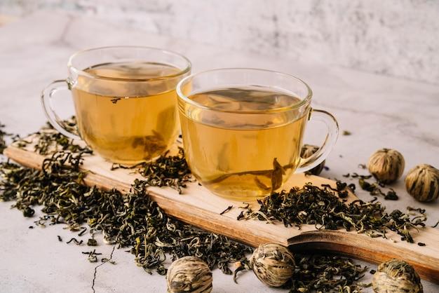Ensemble de vue haute de tasses et d'herbes de thé séchées Photo gratuit