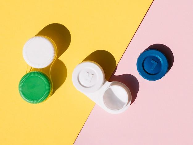 Ensembles de lentilles de contact sur fond orange et rose Photo gratuit