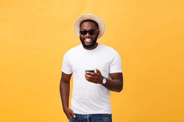 Enthousiaste afro-américain en chemise blanche à l'aide de l'application du téléphone portable. Photo Premium