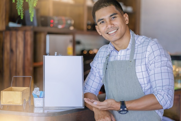 Enthousiaste beau chef d'entreprise permanent avec inviter présent menu devant bar. Photo Premium