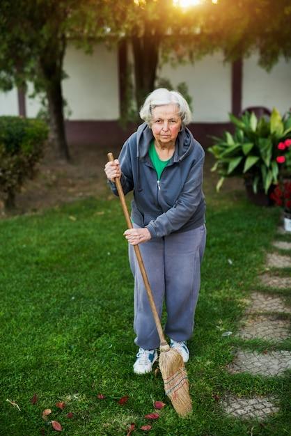 Enthousiaste Femme âgée Tenant Un Balai Dans La Cour De La Maison. Photo Premium