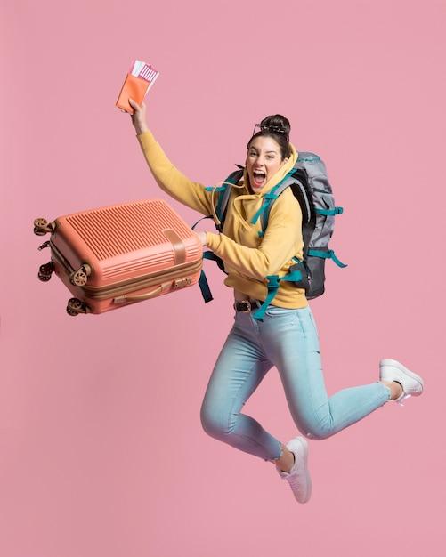 Enthousiaste Femme Tenant Ses Bagages Et Billet D'avion Photo gratuit