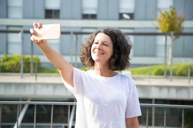 Enthousiaste femme touriste prenant selfie Photo gratuit