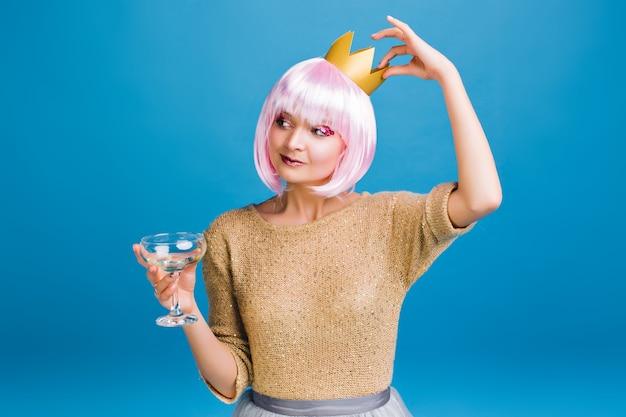 Enthousiaste Incroyable Jeune Femme Avec Coupe De Cheveux Rose S'amuser. Couronne D'or Sur La Tête, Maquillage Lumineux Avec Des Guirlandes Roses, Champagne, Fête Du Nouvel An, Souriant. Photo gratuit