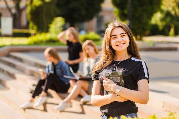Enthousiaste Jeune Adolescente Avec Livre Près D'amis Photo Premium