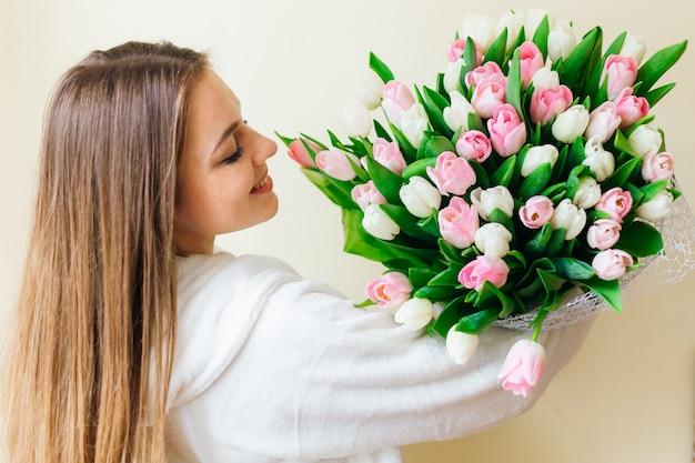 Enthousiaste Jeune Femme Aux Cheveux Longs étant Excité D'obtenir Un Bouquet De Tulipes Roses Le Jour De La Femme Isolée Photo Premium