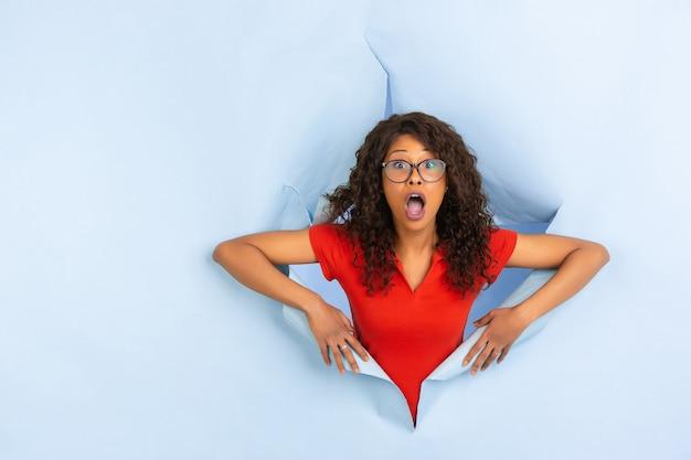 Enthousiaste Jeune Femme Pose En Fond De Trou De Papier Bleu Déchiré, émotionnel Et Expressif Photo gratuit