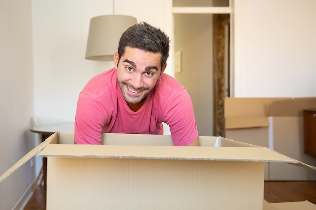 Enthousiaste Jeune Homme Déballage Des Choses Dans Son Nouvel Appartement, Ouverture De La Boîte En Carton, Photo gratuit