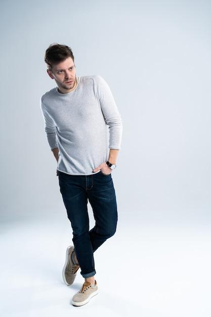 Enthousiaste Jeune Homme Tenant Les Mains Dans Les Poches Et Regardant La Caméra En Se Tenant Debout Sur Fond Blanc Photo Premium