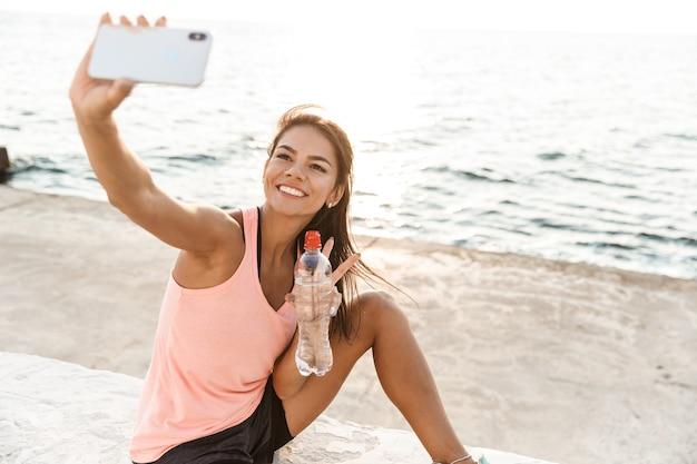 Enthousiaste Jeune Sportive Au Repos Après L'entraînement à La Plage, Prenant Un Selfie, Eau Potable Photo Premium