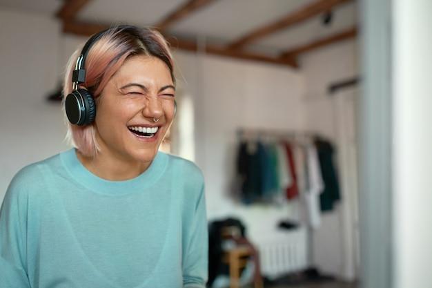 Enthousiaste Positive Jeune Blogueuse Avec Anneau Dans Le Nez En Riant Lors De L'enregistrement D'un Podcast, à L'aide D'un Casque. Photo gratuit