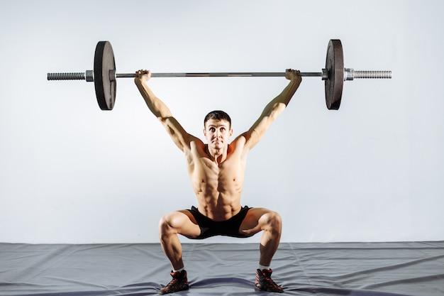 Entraînement musculaire homme avec haltères au gymnase. Photo Premium