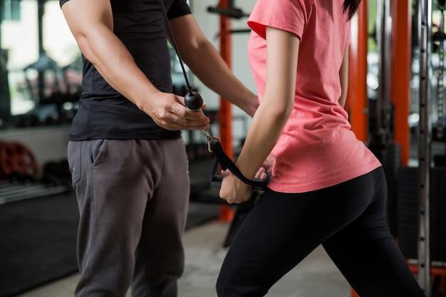 Un entraîneur enseigne correctement aux femmes asiatiques l'entraînement de gym Photo Premium