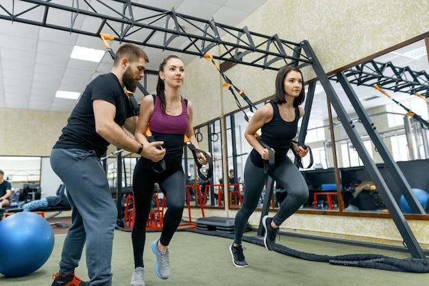 Entraîneur de fitness entraînant et aidant les femmes à faire des exercices Photo Premium