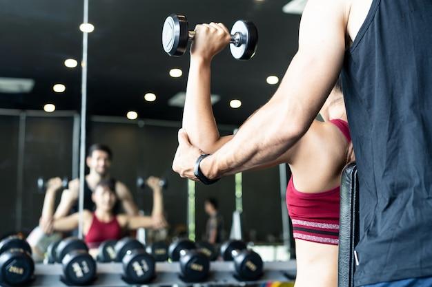 Entraîneur masculin caucasien aidant une jeune femme asiatique à s'entraîner sur le muscle de l'épaule en soulevant des haltères sur les deux bras dans une salle de sport ou un club de fitness. Photo Premium