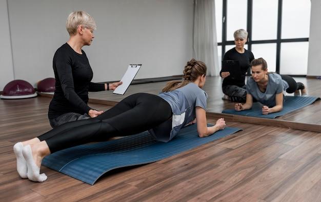 Entraîneur Personnel Féminin Et Son Client Faisant Planche Photo gratuit