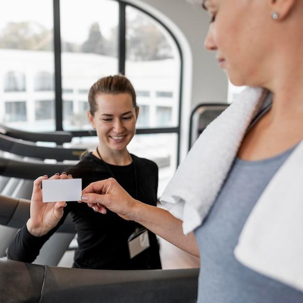 Entraîneur Personnel Féminin Et Son Client Tenant Une Carte Photo gratuit