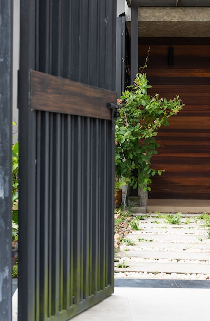 Entrée de clôture de porte stell noir à la maison avec bloc de ciment et passerelle en pierres blanches Photo Premium