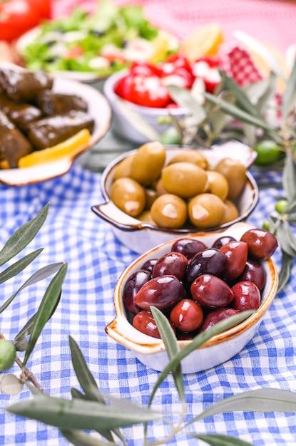 Entrées traditionnelles, olives vertes et rouges de la cuisine grecque. branches fraîches d'olives. fond au dessus de. nappe à carreaux bleus Photo Premium