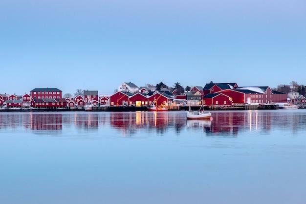 Entrepôt de pêche rouge avec reflet de bateau de pêche sur le littoral Photo Premium