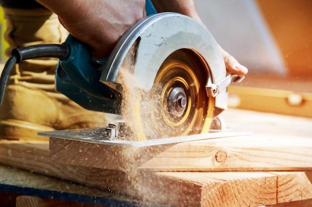 Entrepreneur en construction utilisant une scie circulaire à main à vis sans fin pour couper les planches Photo Premium