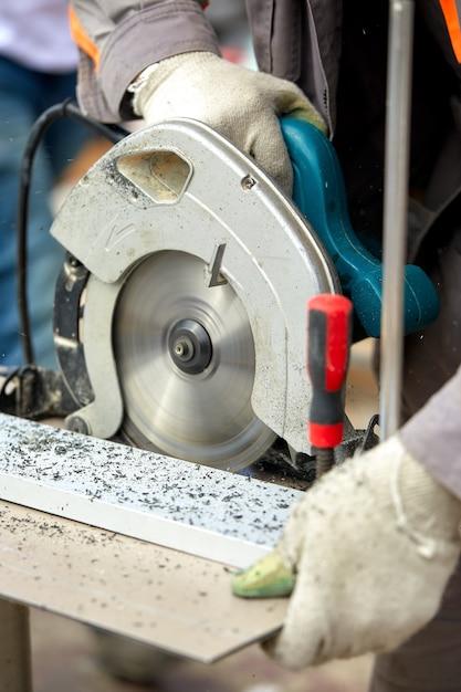 Un entrepreneur en construction utilisant une scie circulaire portative à vis sans fin pour couper les panneaux et le plastique. construction, propre atelier, contrat de travail pour la coupe du bois. Photo Premium