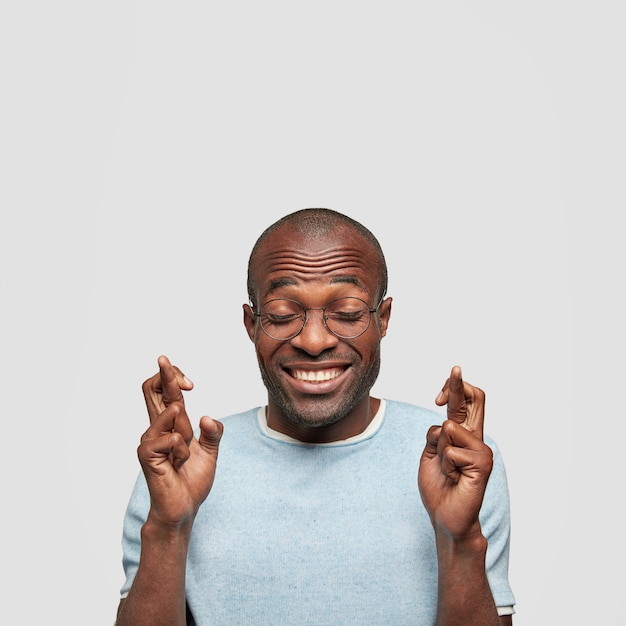 L'entrepreneur Homme Gai Prie Pour Le Succès Ou La Bonne Chance, Garde Les Doigts Croisés Et Les Yeux Fermés, A Un Sourire éclatant Photo gratuit