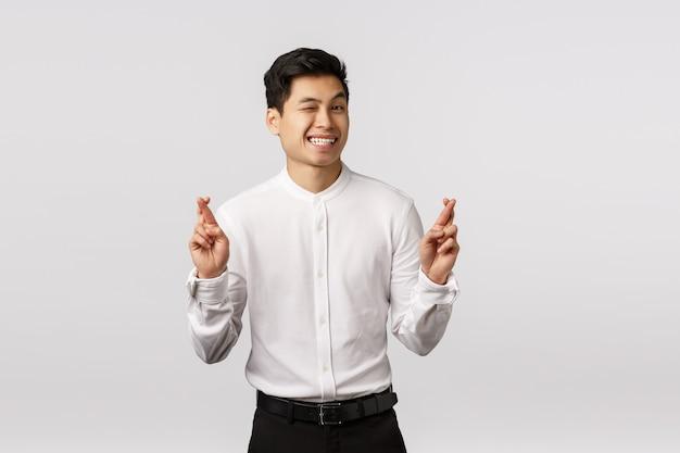 Entrepreneur Masculin Asiatique Optimiste Mignon Optimiste En Chemise Blanche, Pantalon, Appareil Photo Clin D'oeil Effronté, Souriant Assuré Que Tout Va Bien, Croisez Les Doigts Bonne Chance, Prévoyez Une Grosse Affaire Au Travail Signé Photo Premium