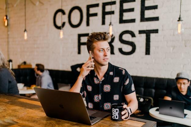 Entrepreneur travaillant avec son ordinateur portable au café Photo gratuit