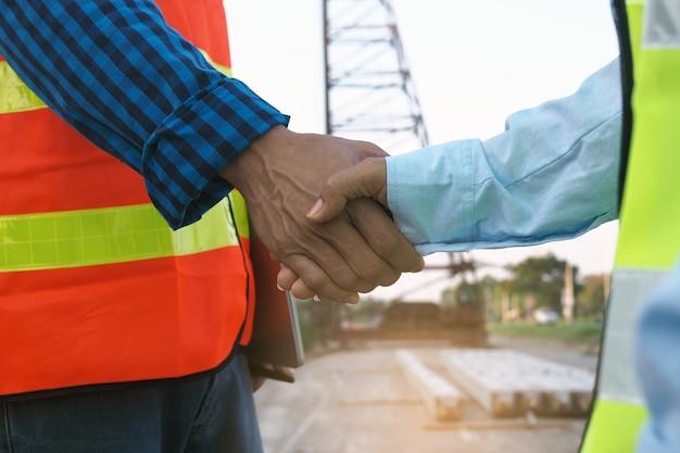 Les entrepreneurs et les ingénieurs se donnent la main pour accepter de travailler ensemble. concept de construction de bâtiments Photo Premium