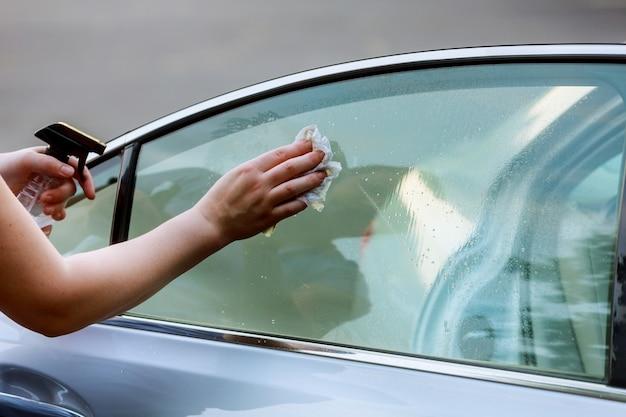 Entretien de voiture - femme lavant une voiture à la main en utilisant un chiffon en microfibre. Photo Premium