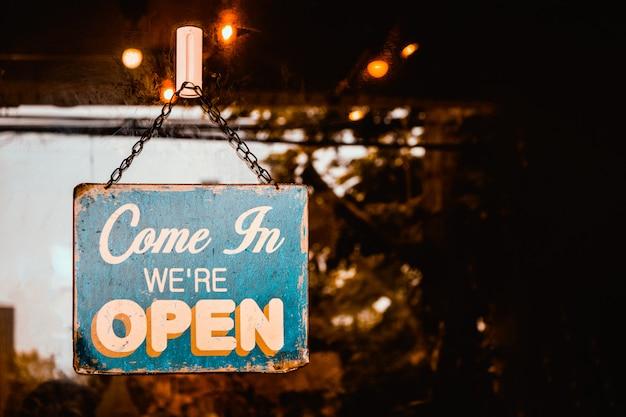 Entrez nous sommes ouverts signe sur la porte du café. Photo Premium