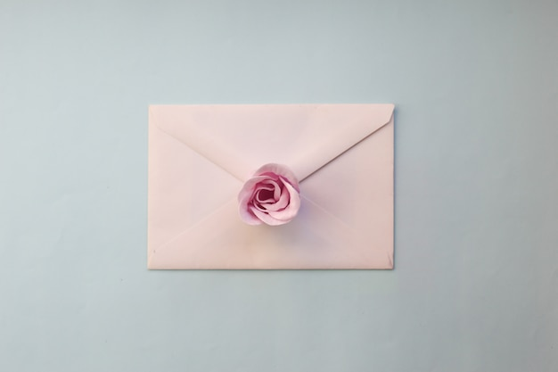 Enveloppe Blanche, Fleur Rose Rose Sur Fond Bleu. Lay Plat Minimal Photo Premium