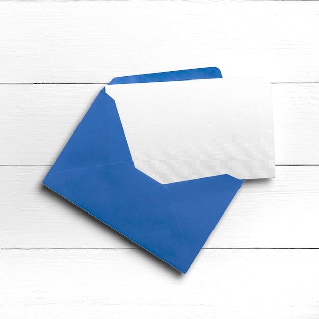 Enveloppe Bleue Avec Carte Postale Ou Carte De Voeux Sur Table En Bois Blanc Photo Premium
